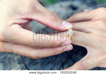groom putting ring on bride's finger on wood background