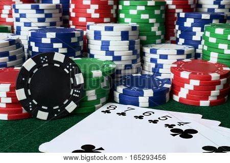 A close up image of stacked poker chips and a straight flush.