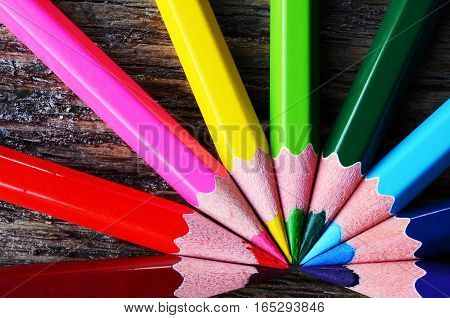 A top view image of brightly coloured pencil crayons in a rainbow pattern.