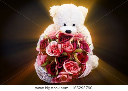 Selective focus at bouquet of beautiful artificial red roses in the arms of blurry white bear doll on black background and ray effect concept love for valentine day or spacial anniversary