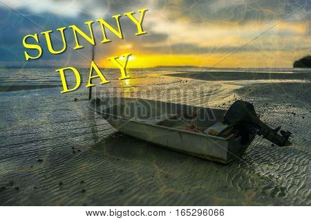 Word Sunny Day on the background with fishing boat on the beach during sunrise.Fishing concept.