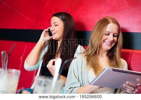friends having fun at a cafe, surfing the internet on their digital tablet