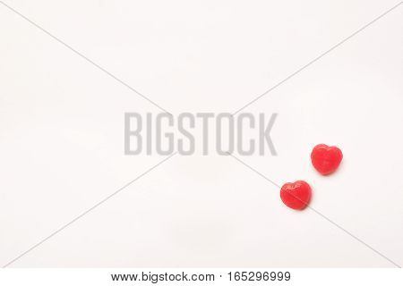 two little Red Valentine's day heart shape candy on empty white paper background. Love Concept. Minimalism style. Knolling top view.