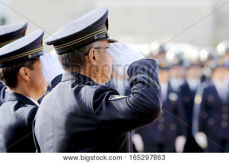 KAGAWA, JAPAN - JANUARY 6: Japanese police officers saluting, stand in a row, Sietusiki ceremony. January 6, 2017 in Kagawa, Japan.