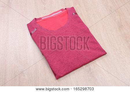 Pink fold sport tshirt on wooden background