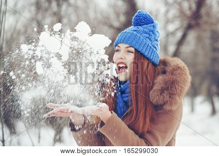 Cute teen girl in blue knitted hat and scarf fur hooded jacket winter walks in the park. She tosses the white snow. Outdoor Activities. Youth fashion. Close-up portrait