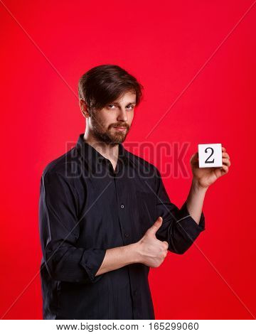 Man holding a cube with the number two. Numerals. Man showing thumb up. Everything gonna be alright.