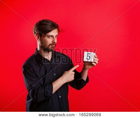 Man holding a cube with the number five. Numerals. The man points his index finger on the cube. Call to action