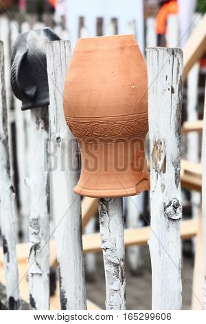 On a fence the burst ceramic jug upside down hangs.