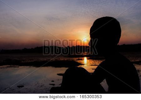 Silhouette Of The Boy Sit Hugged Knees Look The Sunset.
