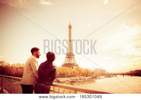 Multi-ethnic couple enjoying their trip to Paris along the Seine river, near Eiffel Tower.