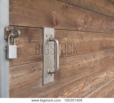 A large wooden sliding door with a big handle has been shut and secured with a padlock.