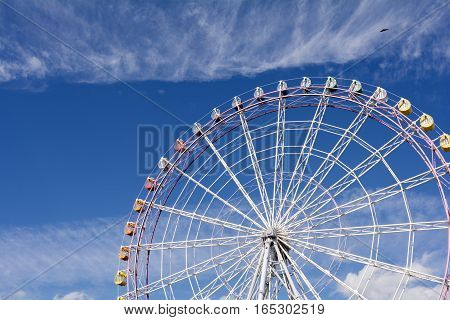 Large ferris wheel facing diagonally under blue sky