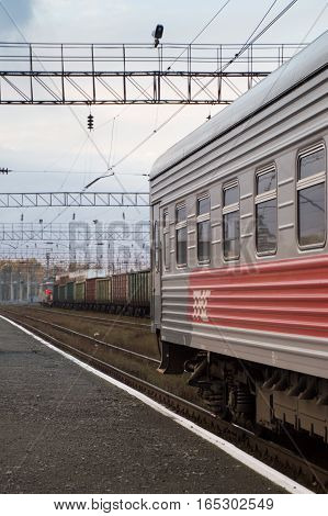 The last car of a train on the Trans-Siberian Railway on the tracks in Russia.  A freight train with multi-colored cars is on the neighboring track. Power lines are above.