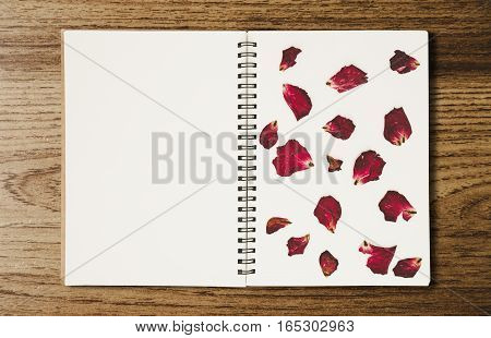 Opened binder blank notebook with rose press rose flower petals, on wood backgrounds