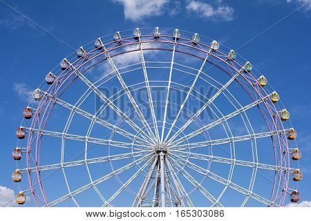 Close up large ferris wheel facing front under blue sky