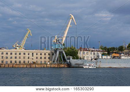 Sevastopol, Russia - June 09, 2016: Lifting cargo cranes at the shipyard in Bay of Black Sea.