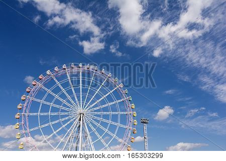 Large ferris wheel facing front under blue sky with clouds
