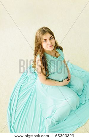 Pregnant young woman in azure dress posing sitting waiting for a miracle concept