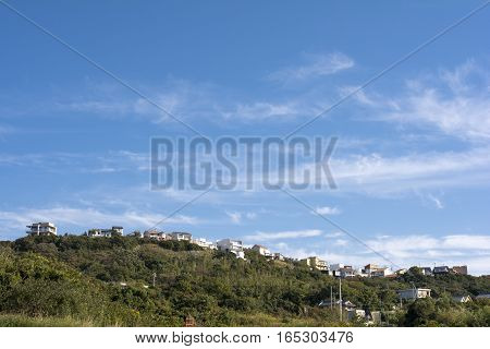 Residential area on a hill under blue sky