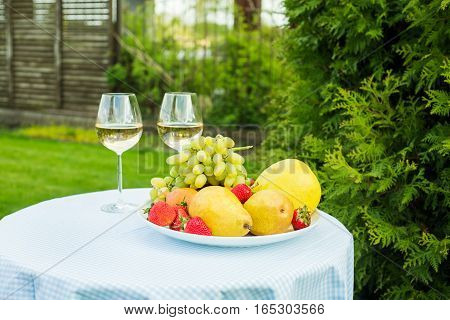fresh fruit on a plate and wineglass with white wine on a table in the garden