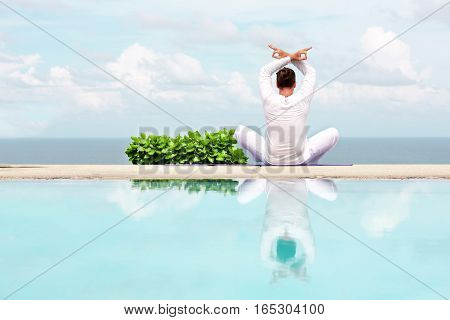 Caucasian man in white clothes meditating yoga on the sea shore pier or platform