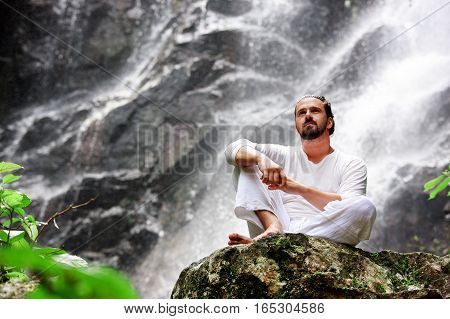 Man sitting in meditation yoga on rock at waterfall in tropical rainforest