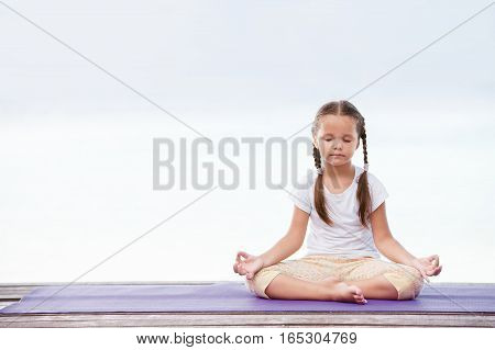 Child doing meditating exercise on wooden platform sea shore outdoors. Healthy lifestyle. Yoga girl