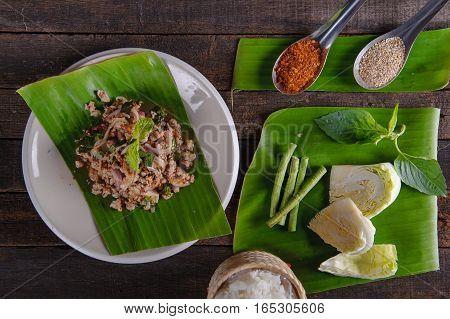 spicy minced pork salad on fresh banana leaf and ingredient
