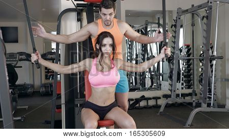 Trainer helping girl to train in the gym. Lady training with dumbbells. Beautiful woman working out with trainer at the gym on the simulator. Attractive sporwear.