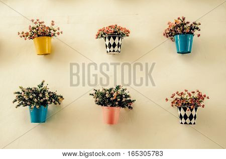 Artificial colorful flower pots hang onto the wall. Processed with vintage stylecan be used for background