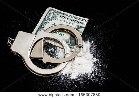 Handcuffs, Money And Drugs On Black Background