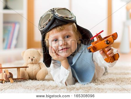 happy child toddler playing with toy airplanes and dreaming of becoming a pilot
