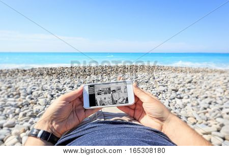 Tourist at the beach checking surveillance cameras at home