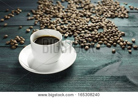 A cup of black coffee on a wooden boards texture, with beans scattered around, with copyspace. A horizontal design template for a cafe or shop