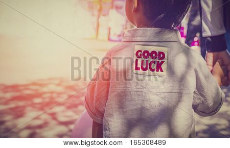 Red printed word good luck on the unidentified little boy shirtsvintage color design.
