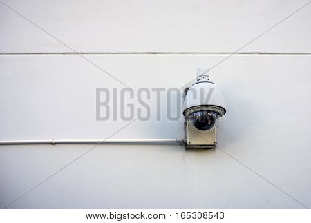 Security camera in a glass cover on concrete wall