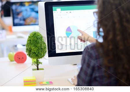 Over the shoulder view of a businesswoman working at computer and pointing to graph on screen