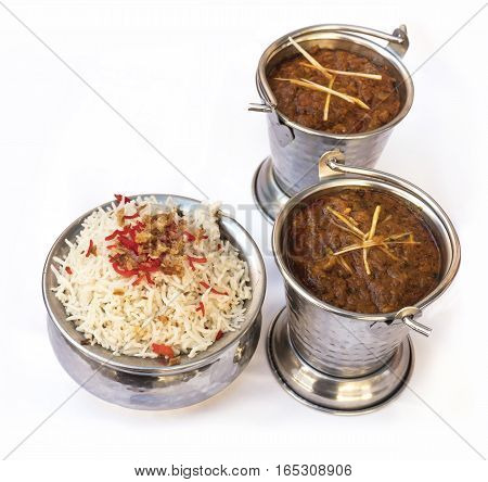 A photo of a bowl of traditional Indian rice, served with two balti dishes, in a typical national cuisine restaurant, on a white background with copyspace