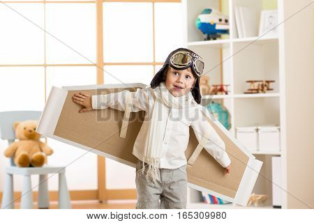 Child boy dressed as pilot or aviator plays with handmade paper wings in his room