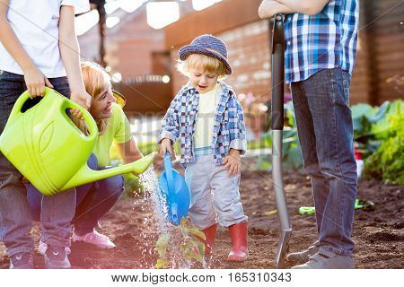 Little boy watering plant with his mother and brothers in garden