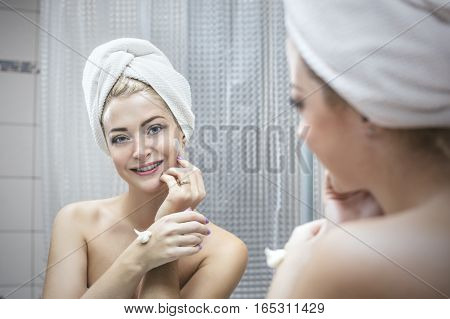 Young Woman In A Bathroom Holds A Cosmetic Procedures To Enhance Beauty And Health