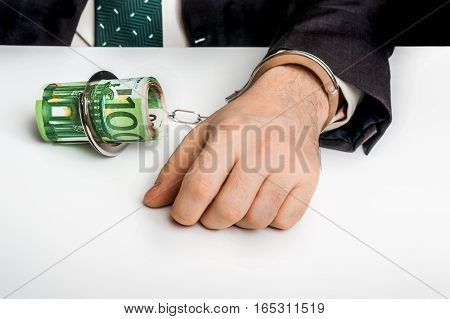 Man In Suit Chained With Handcuffs To Money