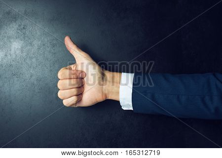 Like this. Close-up of human hand with thumb up in front of the blackboard