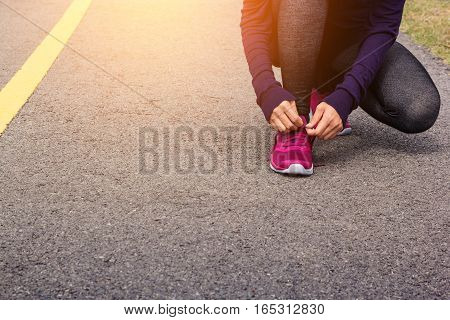 young woman runner tying shoelaces in the morning.