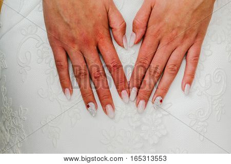 Hands of the bride at a wedding dress. Wedding manicure