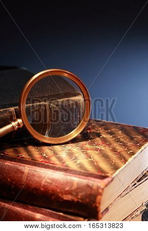 Vintage library. Closeup of magnifying glass on old book