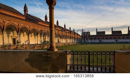 Grand Cloister of the Pavia Carthusian monasteryfeatures columns with precious decorations in terracotta portraying saints prophets and angels in white and pink Verona marbleat sunsetItaly.