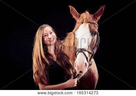 Woman With Her Horse, studio shot on black background.