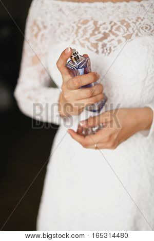 Bride enjoys perfume. He is holding a bottle